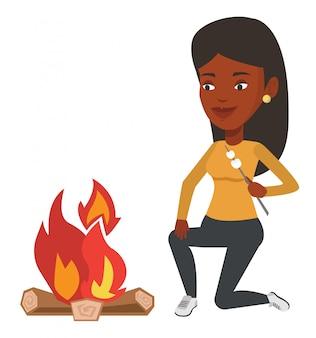 Mulher assar marshmallow sobre fogueira.