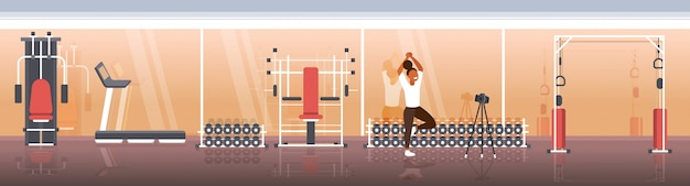 Mulher blogger fazendo yoga exercícios sportswoman gravação de vídeo on-line com câmera no tripé estilo de vida saudável streaming ao vivo conceito moderno ginásio interior horizontal comprimento total