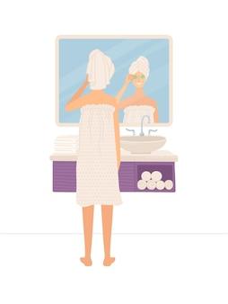 Mulher bonita em pé no banheiro e olhando seu reflexo no espelho