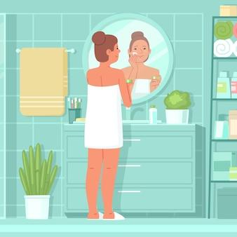 Mulher bonita está no banheiro em frente a um espelho e aplica hidratante no rosto