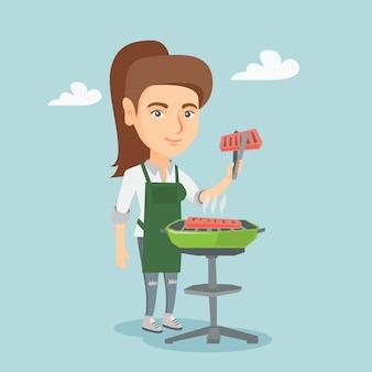 Mulher caucasiana, cozinhar bife no churrasco.