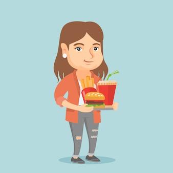 Mulher caucasiana, segurando a bandeja cheia de fast-food.