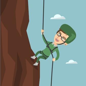 Mulher caucasiana, subindo uma montanha com corda.