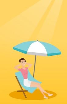 Mulher caucasiano nova que relaxa na cadeira de praia.