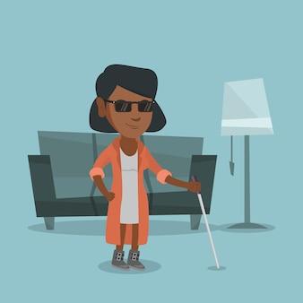 Mulher cega afro-americana nova com uma vara.