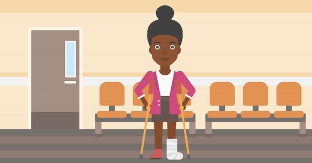 Mulher com a perna quebrada e muletas.