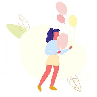 Mulher com algodão doce e balões na mão.