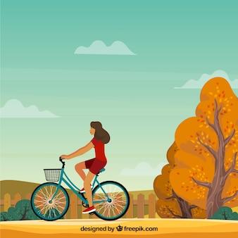 Mulher com bicicleta e paisagem outonal