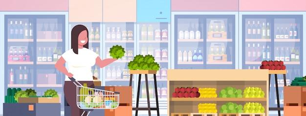 Mulher com carrinho carrinho escolhendo legumes e frutas conceito de perda de peso