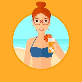 Mulher com coquetel na praia.