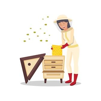 Mulher com favo de mel na mão fica perto de colmeia.