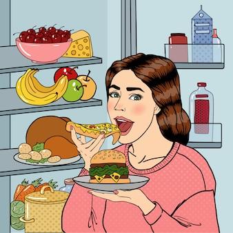 Mulher com fome, comer alimentos pouco saudáveis perto da geladeira.
