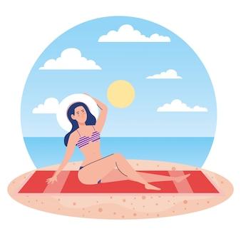 Mulher com maiô sentado na toalha, na praia, temporada de férias