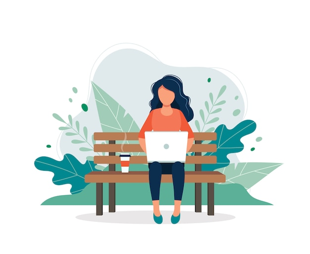 Mulher com o portátil que senta-se no banco na natureza e nas folhas.