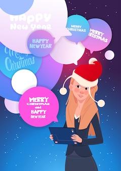 Mulher com tablet digital enviar mensagens saudação com feliz ano novo e feliz natal através de