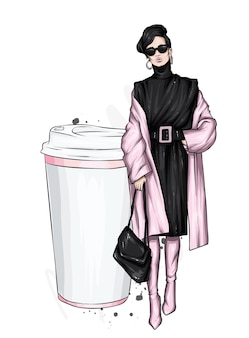 Mulher com um casaco elegante e um copo de café