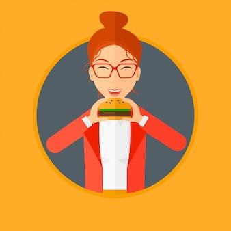 Mulher comendo hambúrguer.