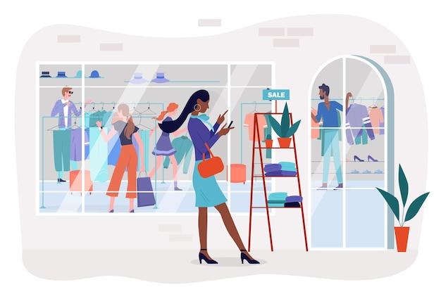 Mulher comprando em uma loja de roupas da moda durante as vendas de desconto em pé com o telefone