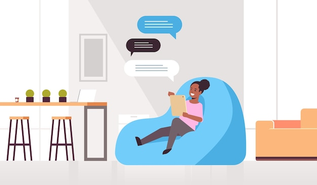 Mulher conversando mensagens garota afro-americana sentada no saco de feijão usando aplicativo móvel comunicação de bolha de bate-papo rede social