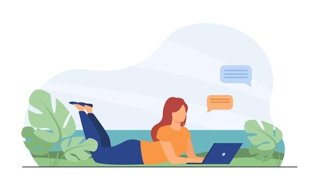 Mulher conversando no laptop e deitada no prado.