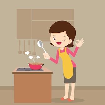 Mulher cozinhando mostrando sinal ok