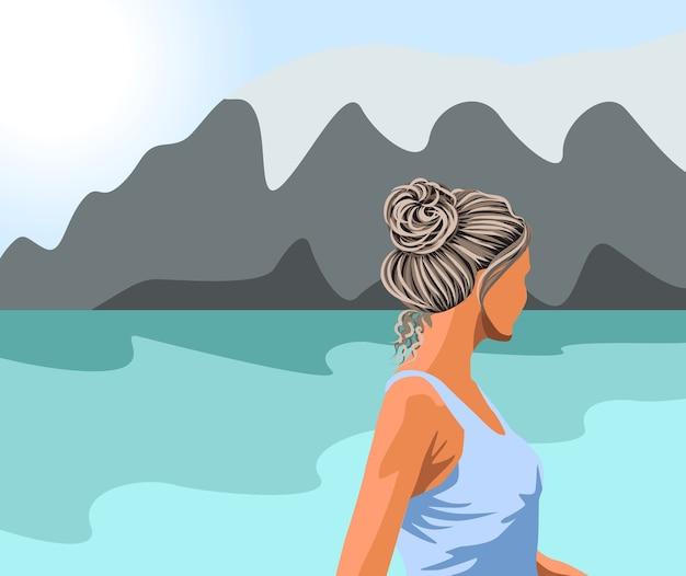Mulher de cabelo grisalho com blusa azul olhando para o lago e as montanhas
