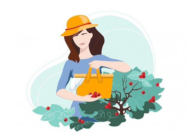Mulher de chapéu colhendo frutas vermelhas em uma sacola no quintal