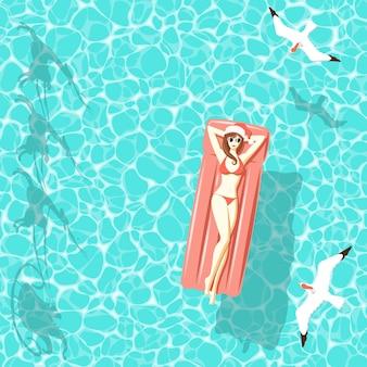 Mulher de natal no colchão de ar no mar