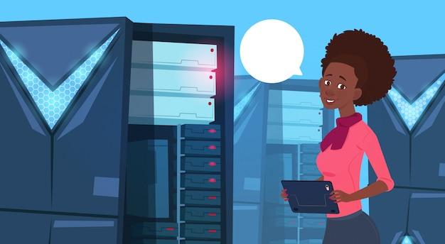 Mulher de negócios americano africano trabalhando em tablet digital no centro de banco de dados moderno ou sala de servidor b