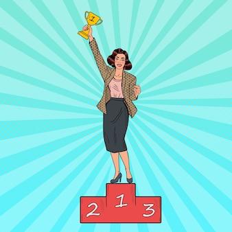 Mulher de negócios de arte pop de pé no pódio primeiro lugar com a taça de ouro.