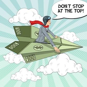 Mulher de negócios de sucesso de arte pop voando em um avião de papel do dólar.