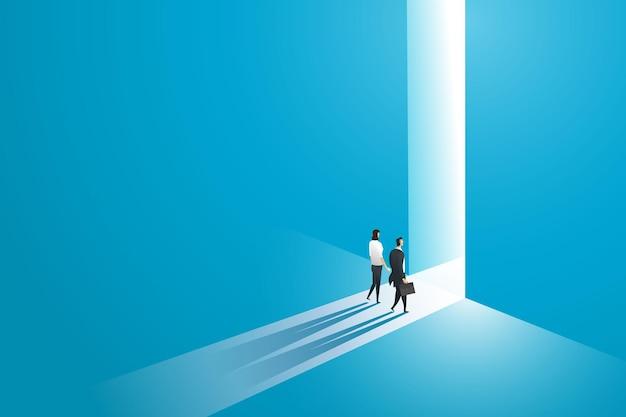Mulher de negócios e empresário caminham para a frente de uma grande porta na parede de um buraco onde a luz atinge