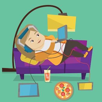 Mulher deitada no sofá com muitos gadgets.