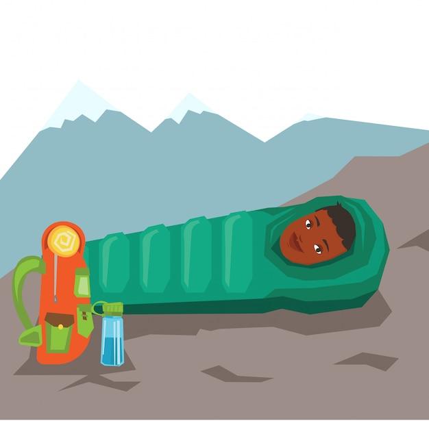 Mulher descansando no saco de dormir nas montanhas.