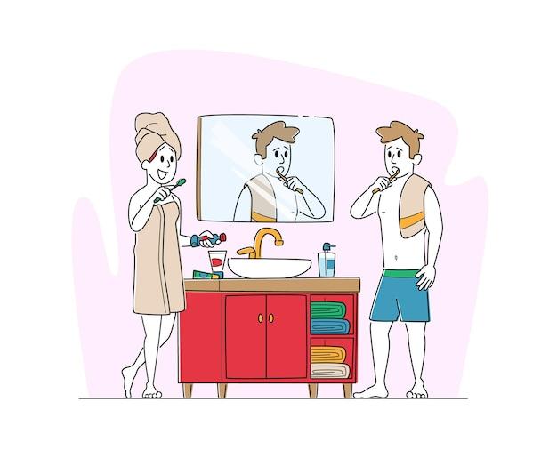 Mulher e homem jovens em frente ao espelho no banheiro e escovando os dentes após o banho ou chuveiro