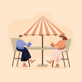 Mulher e homem sentados à mesa com guarda-chuva de verão