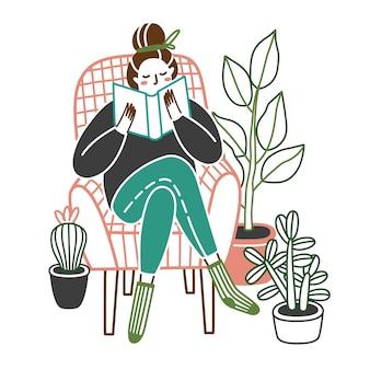 Mulher em casa lendo um livro na cadeira.