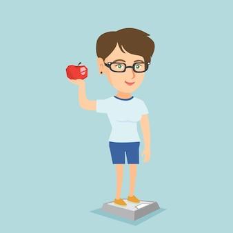 Mulher em pé na balança e segurando a maçã na mão.