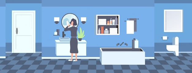 Mulher em roupão, escovar os dentes vista traseira menina olhando no espelho moderno banheiro interior horizontal comprimento total