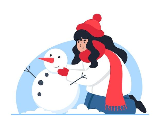 Mulher esculpindo um boneco de neve, caminhada no inverno, clima de natal