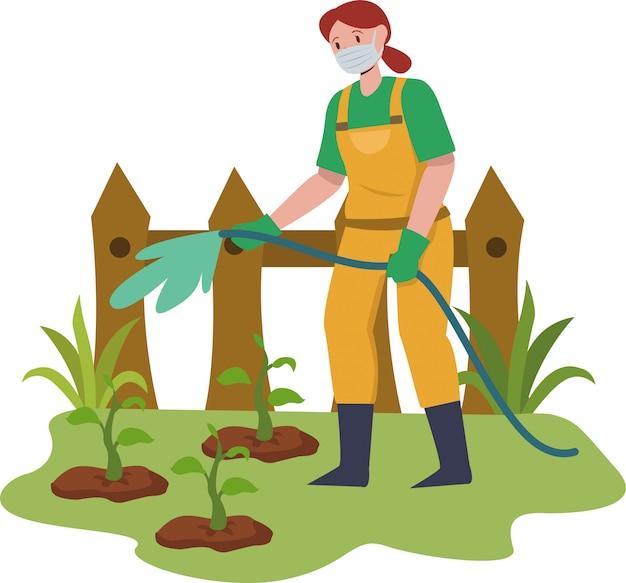 Mulher está molhando as plantas no jardim enquanto estiver usando máscara médica