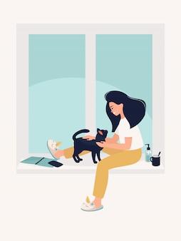 Mulher está sentada e brincando com gato preto na janela em casa.