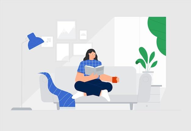 Mulher está sentada em um sofá e lendo um livro em uma sala aconchegante, com fotos na parede, um vaso de flores e uma janela com a natureza.
