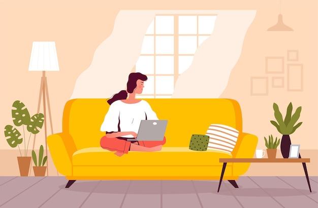 Mulher está sentada no sofá e trabalhando em um laptop