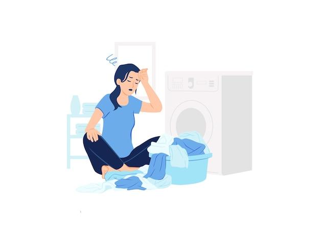 Mulher estressada cansada e oprimida sentada na lavanderia perto da máquina de lavar e uma pilha de roupas sujas.