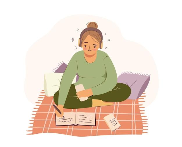 Mulher estudando em um cobertor aconchegante com travesseiros, fones de ouvido, ouvindo música e escrevendo em um bloco de notas