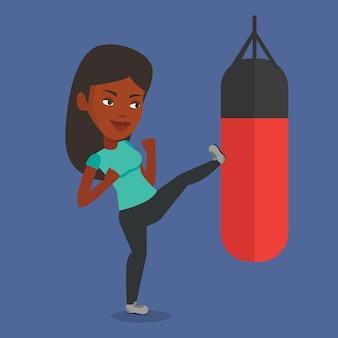 Mulher exercitando com saco de pancadas.
