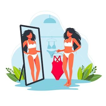 Mulher experimentando maiô inteiro fundido na loja. mulher compras maiô. linda garota escolhendo trajes de banho para as férias de verão no resort tropical. desenho animado feminino experimentando maiô na frente do espelho