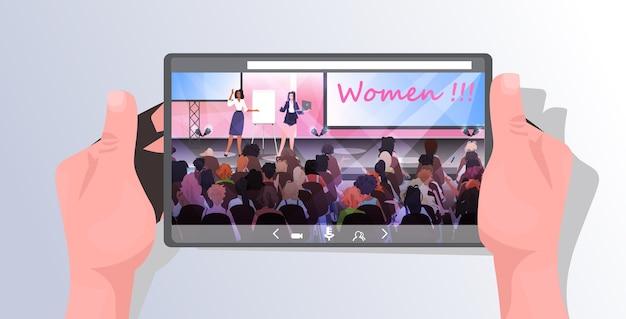 Mulher fazendo apresentação falando para o público do palco meninas do clube feminino apoiando-se mutuamente tela do smartphone do conceito da união de feministas