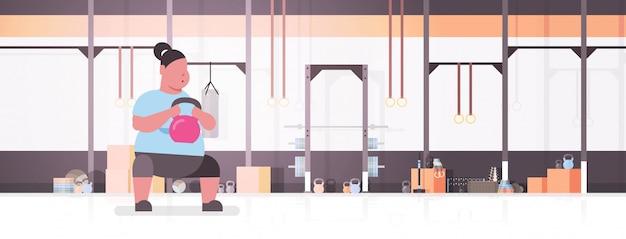 Mulher fazendo exercícios com kettlebell garota gorda treinando no conceito de perda de peso de treino de estúdio de ginástica